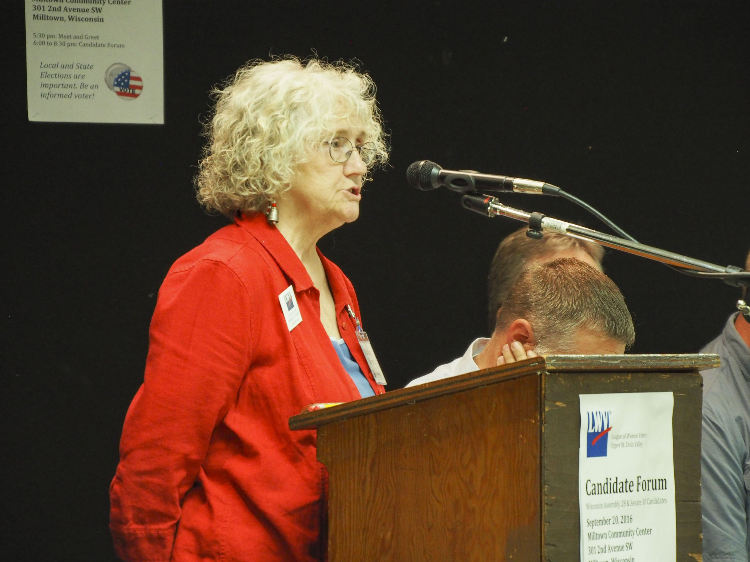 A woman stands at a microphone