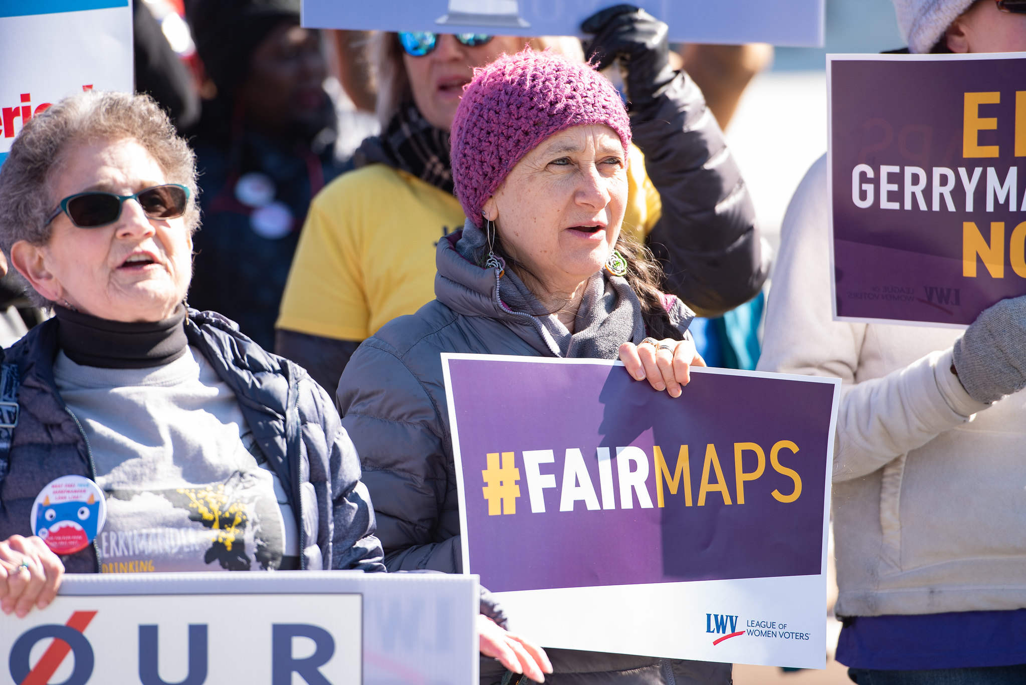 People hold signs about Fair Maps